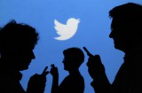 People holding mobile phones are silhouetted against a backdrop projected with the Twitter logo in this illustration picture taken in Warsaw September 27, 2013. Twitter Inc, the eight-year-old online messaging service, gave potential investors their first glance at its financials on Thursday when it publicly filed its IPO documents, setting the stage for one of the most-anticipated debuts in over a year. Picture taken September 27. REUTERS/Kacper Pempel (POLAND - Tags: BUSINESS TELECOMS LOGO)